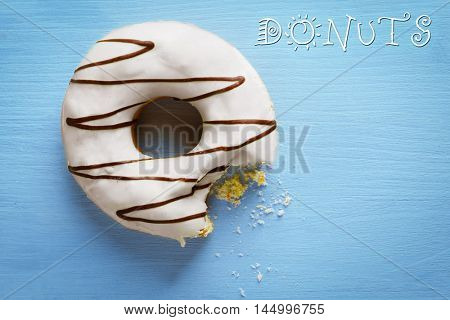 Bitten delicious donut on blue wooden table close-up