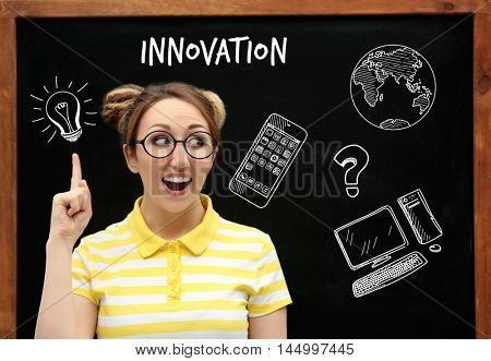 Beautiful young woman on blackboard background. Business trainer concept.