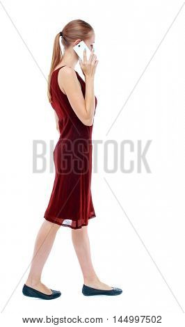 side view of a woman walking with a mobile phone. back view of girl in motion. Isolated over white background. The girl in the maroon sleeveless dress goes sideways and talking on a smartphone.