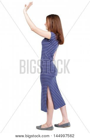 Side view of beautiful woman welcomes. Young teenager girl in jeans hand waving from. Isolated over white background. The brunette in a blue striped dress stands sideways and waving his hand in