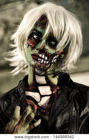 Terrible bloodthirsty zombie woman in the slums. Body-painting project. Glamorous zombie girl. Halloween make-up. Horror.