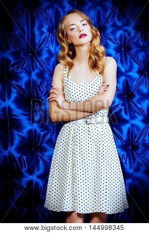 Beautiful young woman with wavy blonde hair posing at studio in light summer dress. Fashion shot. Cosmetics, make-up.