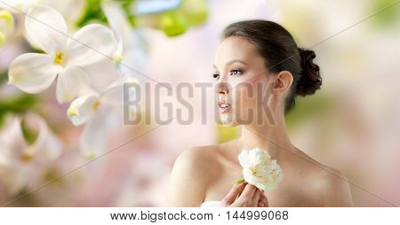beauty, jewelry, people and luxury concept - beautiful asian woman or bride in white dress with peony flower and golden ring over natural spring lilac blossom background