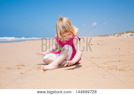Little Child Sitting And Writing With Finger On Sand Beach