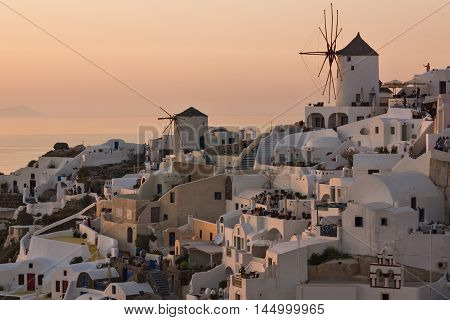 Sunset panorama over white windmills in  town of Oia and panorama to Santorini island, Thira, Cyclades, Greece