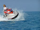 stock photo of jet-ski  - Young woman riding a jet ski on the Mediterranean Sea - JPG