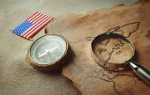 Old map with compass, American flag and magnifier on sand. Happy Columbus day concept poster
