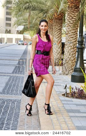 Young Beautiful Woman In The Purple Dress On The Street
