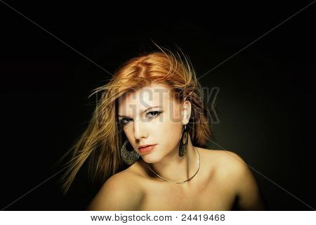 Beauty with shiny golden hair over dark background