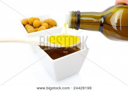 Olive Oil Poured From An Original Bottle Into A Wooden Spoon
