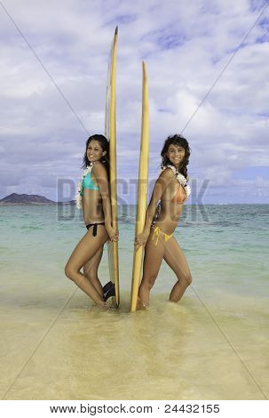 two girls with their surfboards