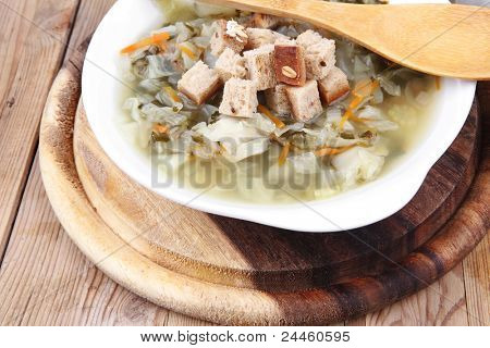 hot fresh diet vegetable soup with rye bread crackers over wood table on stand