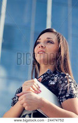 woman holding laptop over glass building, vertical