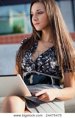 brunette woman working with laptop outdoors
