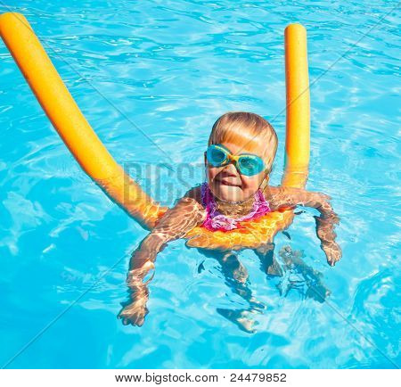 Little girl wearing swimming goggles in a hotel pool