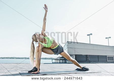 poster of Fit Fitness Woman Doing Stretching Exercises Outdoors At Park. Girl Doing Hamstring Leg Stretching E