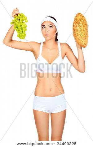 Portrait of a beautiful young woman making choice between loaf and grapes. Isolated over white background.