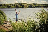 Fisherman Is Fishing On A Fishing Trip. Fisherman Cast Fishing Rod In Lake Or River Water. Man Fish  poster