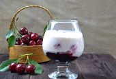 Cherry Yogurt Dessert Or Pudding And Ripe Cherry On A Wooden Table. Summer Dessert. poster