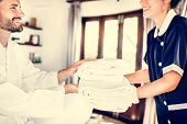 Housekeeper handing over fresh towels poster