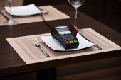 Payment With Credit Card. Credit Card Terminal Near Glasses And Plates On Table Background. Credit C poster