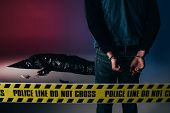 Man In Cuffs By Dead Body Behind Yellow Line On Dark Background poster