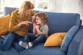 Cheerful Mom Is Enjoying Playing With Her Son While They Are Located On Couch. She Is Pointing Finge poster