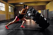 Wheel Truck Exercises At Gym By Young Muscular Woman poster