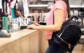 Woman At Checkout In Fashion Store Paying With Credit Card. Customer Using Payment Terminal Machine. poster