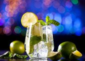 Closeup Of Mojito Cocktail On A Bar Lights Background. Ingredients And Utensils. poster