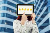 Young Businesswoman Covering Her Face Using A Digital Tablet With Five Golden Stars On The Screen Tr poster