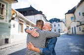 An Adult Hipster Son And His Happy Senior Father In Town, Hugging. poster