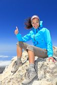 Hiker woman at mountain top summit enjoying view giving success thumbs up sign smiling happy of her