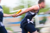 Motion blurred relay race at a track and field event poster