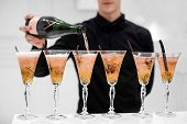 Crop View Of Faceless Waiter In Black Shirt Making Alcoholic Cocktails And Adding Champagne In Glass poster