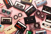 Heap Of Retro Audio Cassette Tapes On Pink Background. Top View On Vintage Media Devices, Copy Space poster