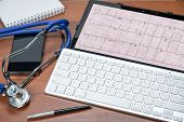 Doctors Table With Tablet Pc And Electrocardiogram On It. Stethoscope And Pen. Healthcare And Medic poster