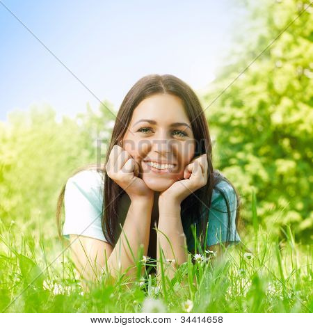 Beauty Young Woman Relaxing On Grass