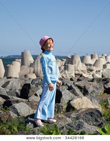 little girl in tracksuit stand on rocks near concrete block
