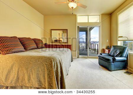 Schlafzimmer mit großem Bett, blauen Stuhl und Bbalcony Tür.