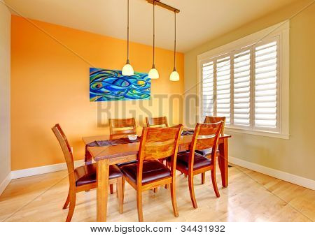 Dining Room With Blue Painting And Wood Table.