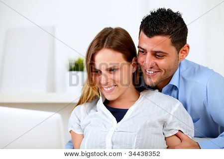 Lovely Young Couple Browsing Internet On Laptop