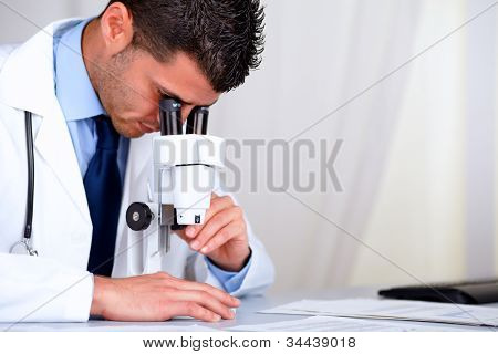 Young Attractive Doctor Working With A Microscope