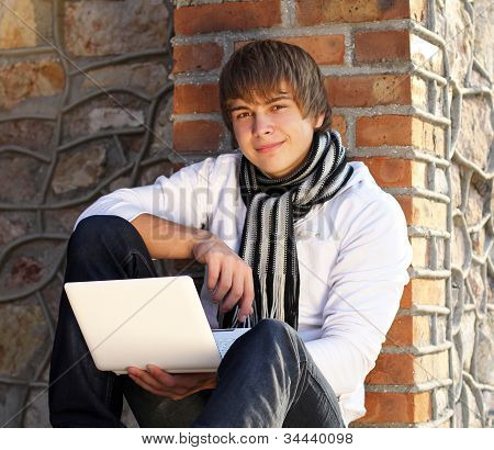 Young Man With Laptop Leaning Against The Brick Wall