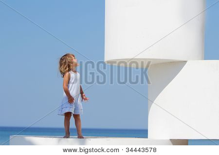 outdoor portrait of young happy girl on big white cubes isolated over blue sky