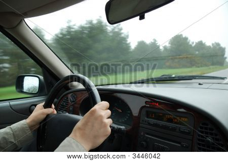 Male Hands Hold Steering Wheel And Landscape Running Through Windshield