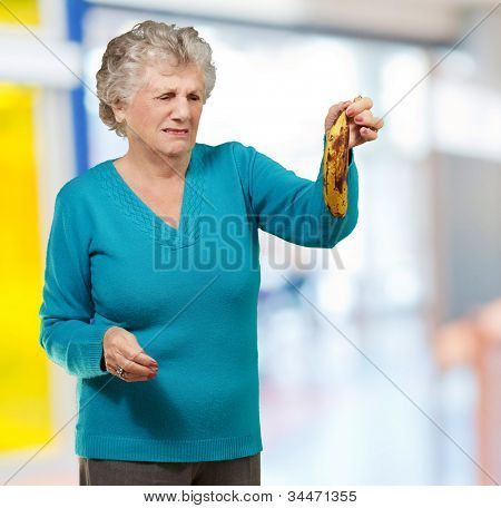 Senior woman holding a rotten banana indoor
