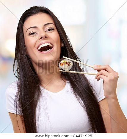 portrait of a young woman holding sushi indoor