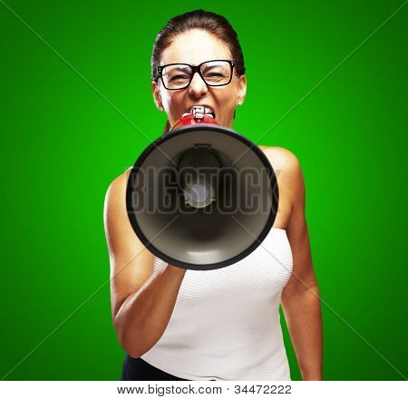 portrait of a middle aged woman shouting with a megaphone over a green background