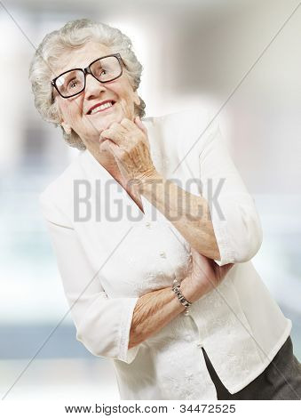portrait of a senior woman thinking and looking up, indoor